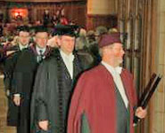 A University Ceremonial Officer (Professor Dick Clements) leads one of the stage parties from the Great Hall at the end of the degree congregation.