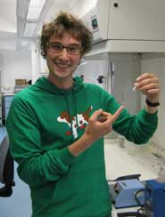 Nick Crumpton holding a specimen tube containing a molar tooth belonging to the early mammal, Morganucodon