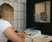 An audiologist conducting an audiometric hearing test in a sound-proof testing booth