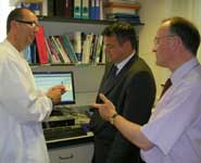Dr Pat Kehoe (Bristol University) explains to Neil McDonald of Bunzl Healthcare (centre) and Mark Poarch of BRACE why the BioAnalyser is an invaluable tool
