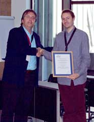 Dr Georg Fuchsbauer (right) receives his award at the 7th International Workshop on Security and Trust Management (STM) in Copenhagen from STM working group chair, Professor Javier Lopez