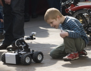 A young pupil is fascinated by one of the robots