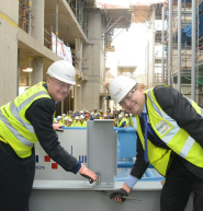 Professor Eric Thomas, Vice-Chancellor of the University of Bristol, with Paul Tuplin, Commercial Director for VINCI Construction UK, tighten a bolt to mark the topping-out of the new Life Sciences building