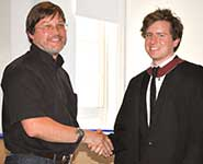 Glenn Farrall from Infineon presenting Mike O'Connor from the Department of Computer Science with his prize awarded for the best student project in computer architecture