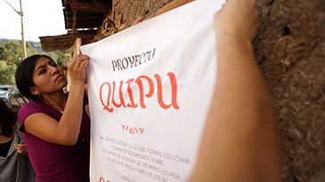 Image of people putting up a Quipu Project poster in Peru