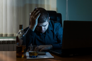 Generic image of a man feeling suicidal in front of a computer