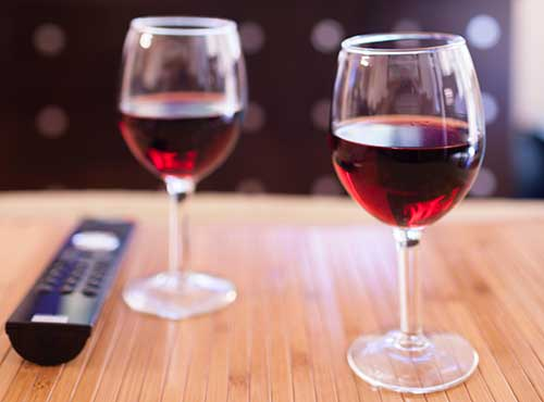 Image of two wine glasses and a remote control