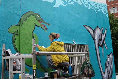 Image of Alex Lucas creating the Uncertain World mural