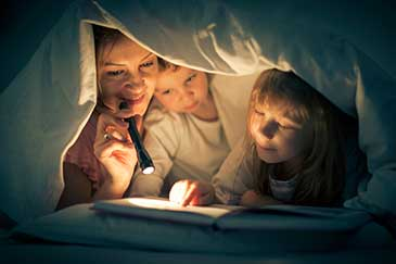 Image of a mother and children reading under the covers