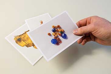 Image of a hand holding a photograph of some beads